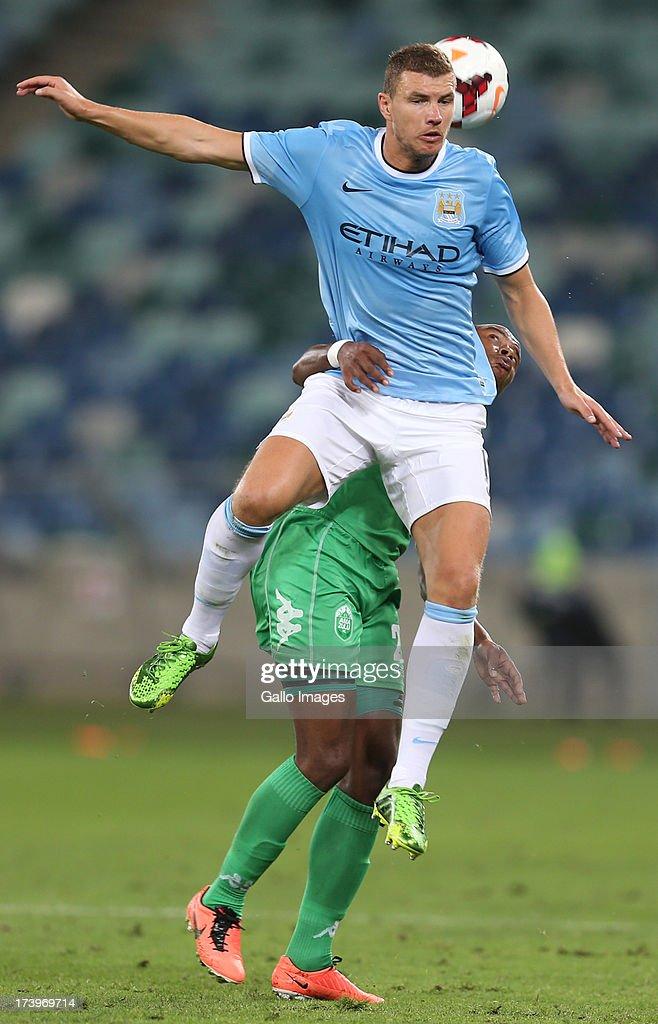 Edin Dzeko of Manchester City jumps into Tamsanqa Teyise of AmaZulu during the Nelson Mandela Football Invitational match between AmaZulu and Manchester City at Moses Mabhida Stadium on July 18, 2013 in Durban, South Africa.