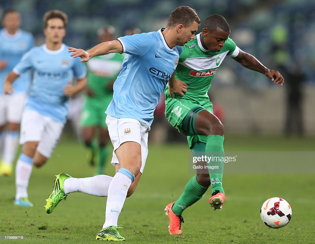 Edin Dzeko of Manchester City looks to make a tackle on Tamsanqa Teyise of AmaZulu during the Nelson Mandela Football Invitational match between AmaZulu and Manchester City at Moses Mabhida Stadium on July 18, 2013 in Durban, South Africa.
