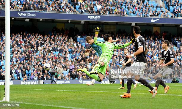 Edin Dzeko of Manchester City scores his team's third goal past goalkeeper Paulo Gazzaniga of Southampton during the Barclays Premier League match...