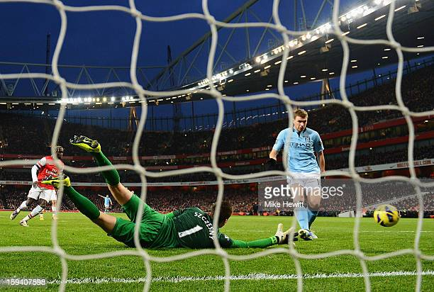 Edin Dzeko of Manchester City shoots past Wojciech Szczesny of Arsenal to score their second goal during the Barclays Premier League match between...