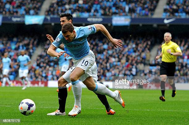 Edin Dzeko of Manchester City wins a penalty as he is brought down by Jose Fonte of Southampton under the watchful eye of Referee Chris Foy during...