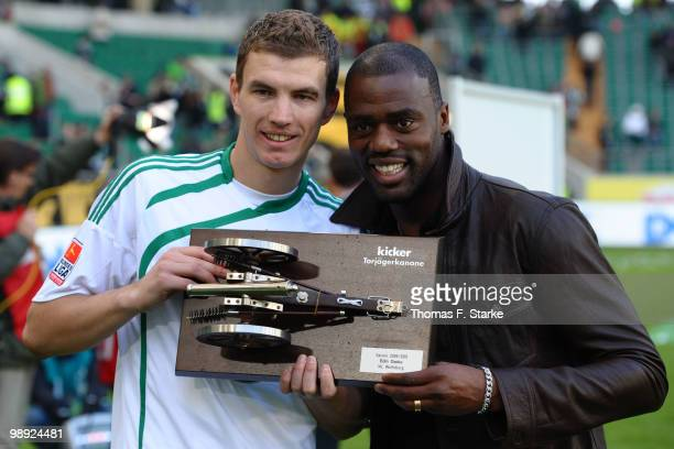 Edin Dzeko of Wolfsburg and last years winner Grafite hold the trophy for best scorer of the season after the Bundesliga match between VfL Wolfsburg...