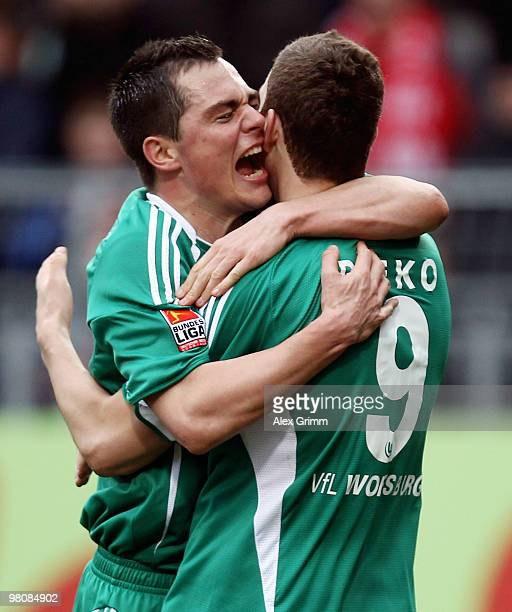 Edin Dzeko of Wolfsburg celebrates after scoring his team's first goal with team mate Marcel Schaefer during the Bundesliga match between FSV Mainz...