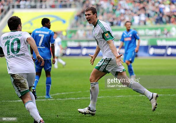 Edin Dzeko of Wolfsburg celebrates scoring his team's first goal with Zvjezdan Misimovic during the Bundesliga match between VfL Wolfsburg and 1899...