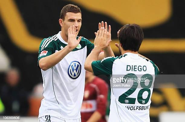 Edin Dzeko of Wolfsburg celebrates with his team mate Diego after scoring his team's first goal during the Bundesliga match between VfL Wolfsburg and...