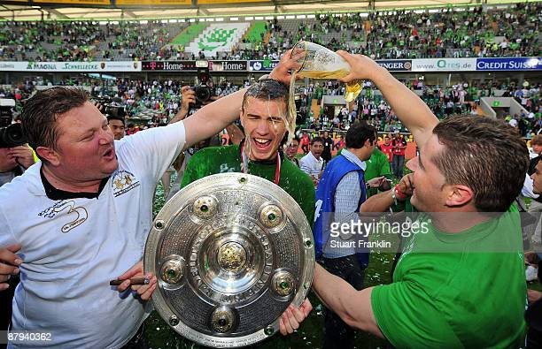 Edin Dzeko of Wolfsburg gets a beer shower by fans celebrating the German championship with the trophy after their Bundesliga match against SV Werder...
