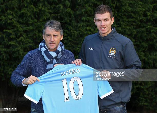 Edin Dzeko the new signing for Manchester City poses with Roberto Mancini the manager of Manchester City during a photocall at the Carrington...