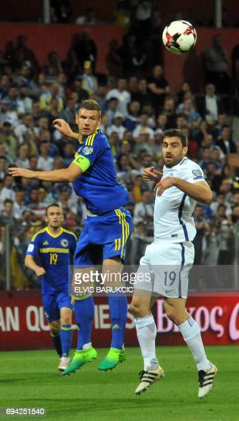 Edin Dzeko vies with Sokiratis Papastathopoulos during the FIFA World Cup 2018 qualification football match between Bosnia Herzegovina and Greece in...
