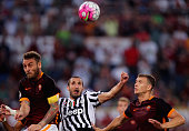 Edin Dzeko with his teammate Daniele De Rossi of AS Roma competes for the ball with Giorgio Chiellini of Juventus FC during the Serie A match between...