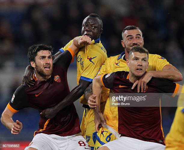 Edin Dzeko with his teammate Ervin Zukanovic of AS Roma compete for the ball with Leonardo Blanchard and Raman Chibsah of Frosinone Calcio during the...