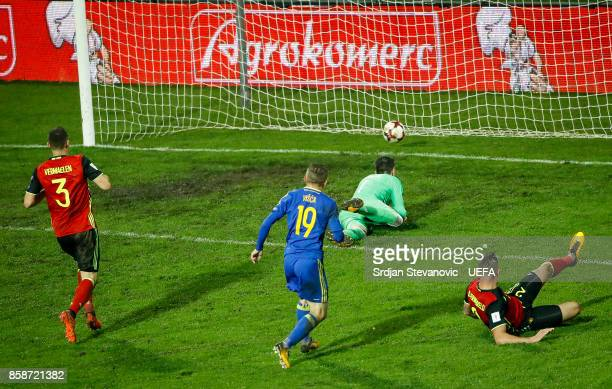 Edin Visca of Bosnia scores the goal near goalkeeper Thibaut Courtois Thomas Vermaelen and Toby Alderweireld of Belgium during the FIFA 2018 World...