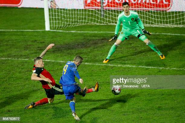 Edin Visca of Bosnia scores the goal near Toby Alderweireld and goalkeeper Thibaut Courtois of Belgium during the FIFA 2018 World Cup Qualifier...