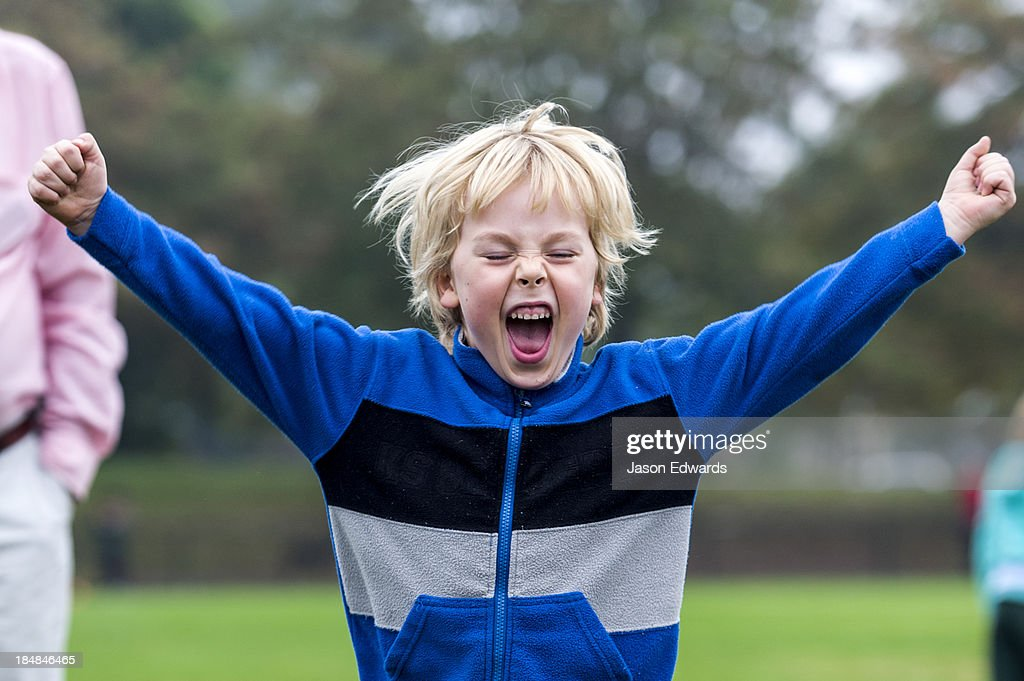 A boy celebrates after kicking a goal at a football training camp.