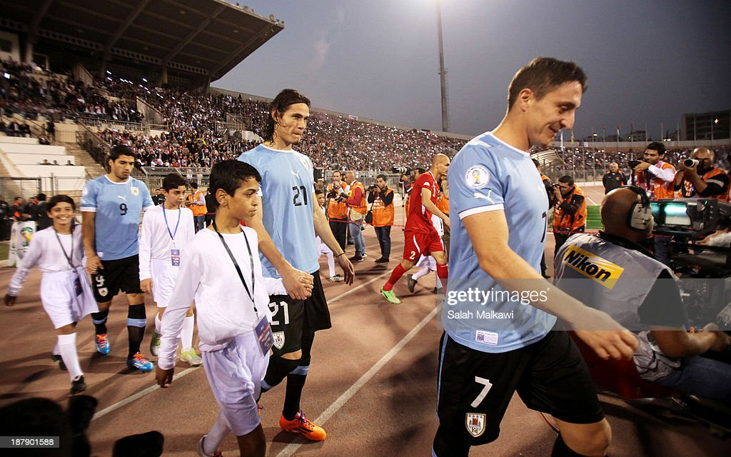 <a gi-track='captionPersonalityLinkClicked' href=/galleries/search?phrase=Edinson+Cavani&family=editorial&specificpeople=4104253 ng-click='$event.stopPropagation()'>Edinson Cavani</a> of Uruguay walks onto the field with teammates during the FIFA 2014 World Cup Qualifier: Intercontinental Play-off First Leg between Jordan and Uruguay on November 13, 2013 in Amman, Jordan.