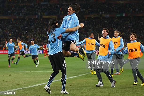Edinson Cavani runs to celebrate with Sebastian Abreu of Uruguay after he scored the winning penalty in a penalty shoot out during the 2010 FIFA...