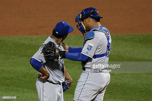 Edinson Volquez of the Kansas City Royals meets with Salvador Perez of the Kansas City Royals on the pitcher's mound in the sixth inning against the...