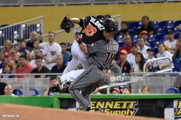 Edinson Volquez of the Miami Marlins and Reymond Fuentes of the Arizona Diamondbacks collide at first base during the first inning at Marlins Park on...