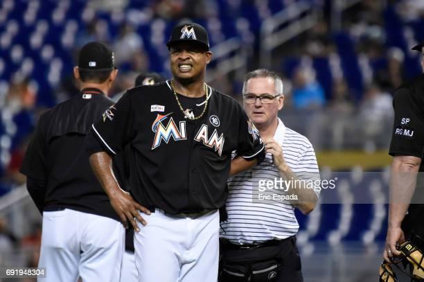 Edinson Volquez of the Miami Marlins walks with Athletic trainer Mike Kozak after colliding with Reymond Fuentes of the Arizona Diamondbacks during...