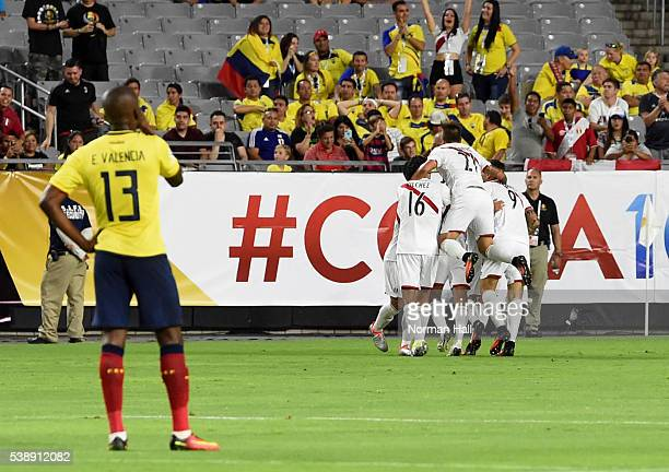 Edison Flores of Peru celebrates with teammates after scoring the second goal of his team as Enner Valencia of Ecuador looks on during a group B...