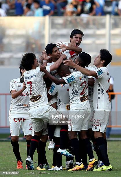 Edison Flores of Universitario celebrates with teammates after scoring the first goal of his team during a match between Sporting Cristal and...