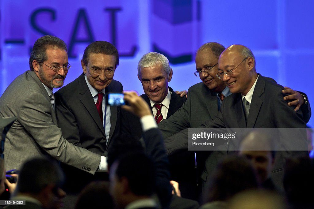 Edison Lobao, Brazil's minister of energy and mines, second from left, poses for photos with Oswaldo Pedrosa, president of Pre-Sal Petroleo, known as PPSA, center, and other execuutives following an auction for the right to develop pre-salt oilfields, in Rio de Janeiro, Brazil, on Monday, Oct. 21, 2013. A group led by Petroleo Brasileiro SA won a license to develop Brazils biggest oil discovery under more favorable terms than analysts estimated. Shares in Petrobras, as the state-run producer is known, surged. Photographer: Dado Galdieri/Bloomberg via Getty Images