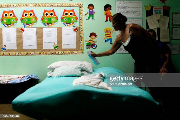 Edith Badillo sprays disinfectant to a cot at a shelter as Hurricane Maria approaches Puerto Rico in Fajardo on September 19 2017 Maria headed...