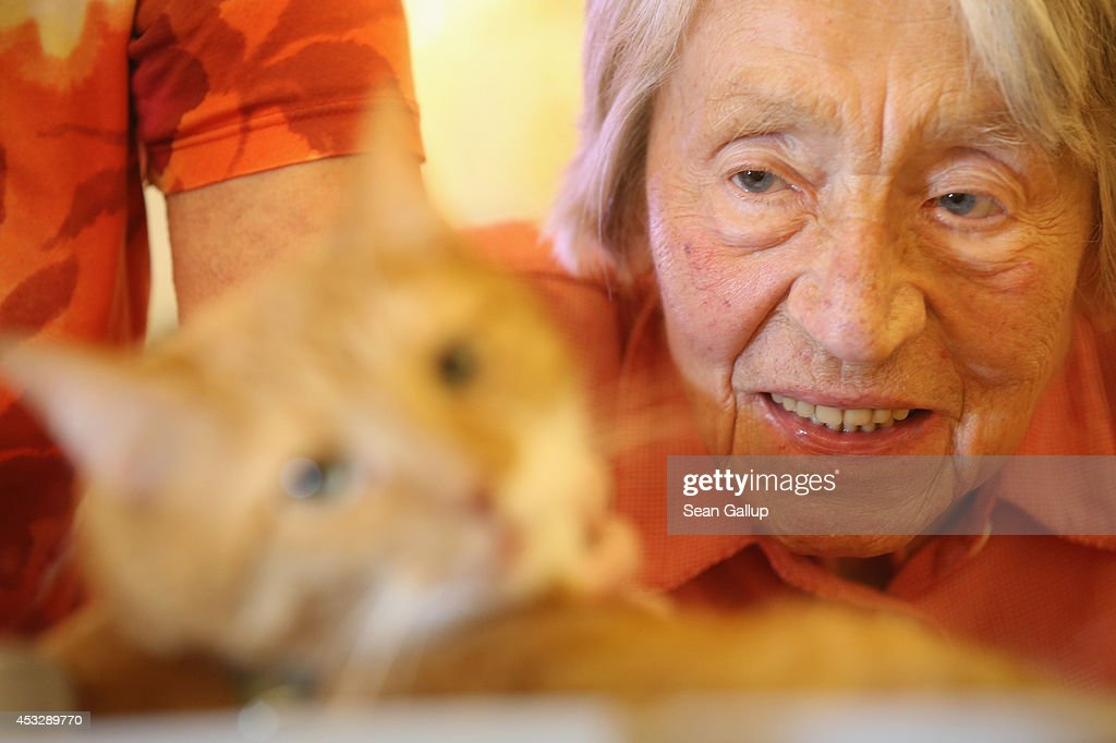 Edith Ehninger who suffers from dementia strokes the fur of Mogli during the cat's weekly visit at the Lutherstift senior care facility on August 6...