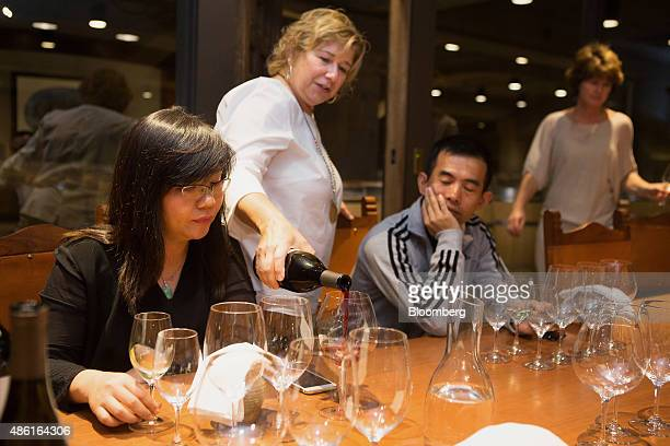 Edith Huang senior director of fast moving consumer goods at Tmallcom for Alibaba Group Holding Ltd left is poured a glass of wine by Trade Wine...