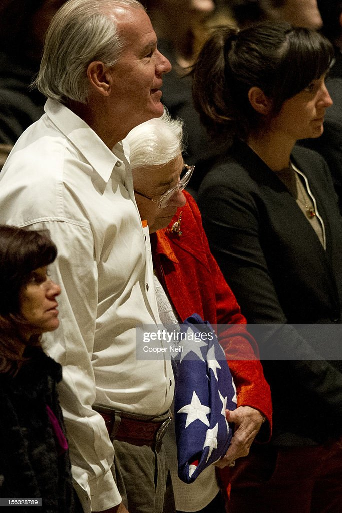 Edith Royal rests her head on son Sammy Mack Royal as she holds the flag presented to her during a memorial service in honor of her late husband and former University of Texas Longhorns head coach Darrell K Royal on November 13, 2012 at the Frank Erwin Center in Austin, Texas.