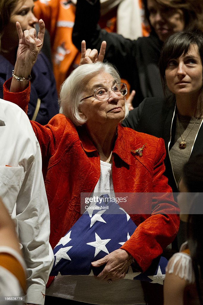 Edith Royal surrounded by family holds the flag presented to her during a memorial service in honor of her late husband and former University of...