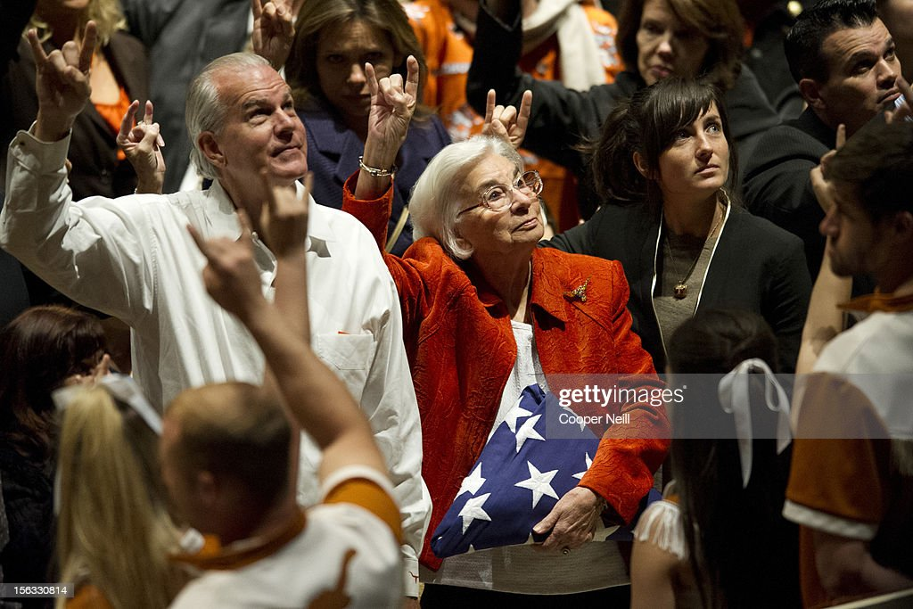 Edith Royal, surrounded by family, holds the flag presented to her during a memorial service in honor of her late husband and former University of Texas Longhorns head coach Darrell K Royal on November 13, 2012 at the Frank Erwin Center in Austin, Texas.