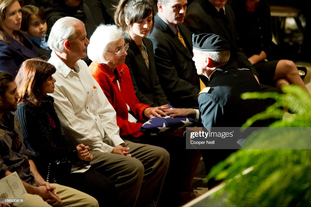 Edith Royal, surrounded by family, is presented a flag by the University of Texas Army ROTC during a memorial service in honor of her late husband and former University of Texas Longhorns head coach Darrell K Royal on November 13, 2012 at the Frank Erwin Center in Austin, Texas.