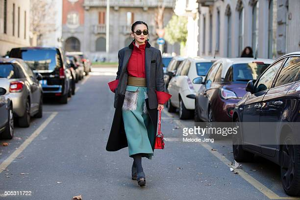 Editor Sherry Shen wears a dark gray blazer with a innerred lining buttonup red top an olive green belt and a green Marni double worsted fur pocket...