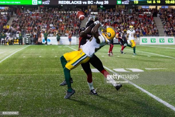 Edmonton Eskimos wide receiver Bryant Mitchell tries to make a catch as he battles Ottawa RedBlacks defensive back Adrian James during Canadian...