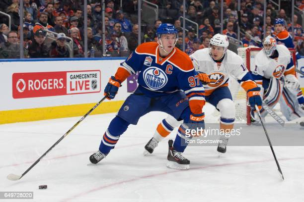 Edmonton Oilers Center Connor McDavid looks for a team mate to pass to before New York Islanders Center Ryan Strome can intercept the puck on March 7...