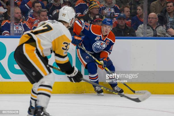 Edmonton Oilers Center Connor McDavid looks to pass the puck around Pittsburgh Penguins Right Wing Carter Rowney on March 10 2017 at Rogers Place in...