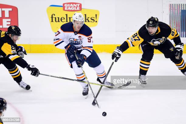 Edmonton Oilers Center Connor McDavid stickhandles with the puck between Pittsburgh Penguins defenseman Brian Dumoulin and Pittsburgh Penguins center...