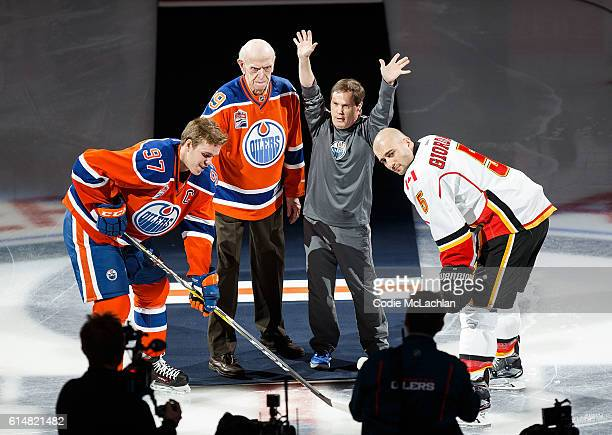 Edmonton Oilers locker room attendant Joey Moss raises his hands in the air as he takes part in the opening puck drop between Connor McDavid of the...