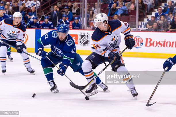 Edmonton Oilers right wing Kailer Yamamoto and Vancouver Canucks center Alexander Burmistrov fight for the puck during their NHL preseason game at...