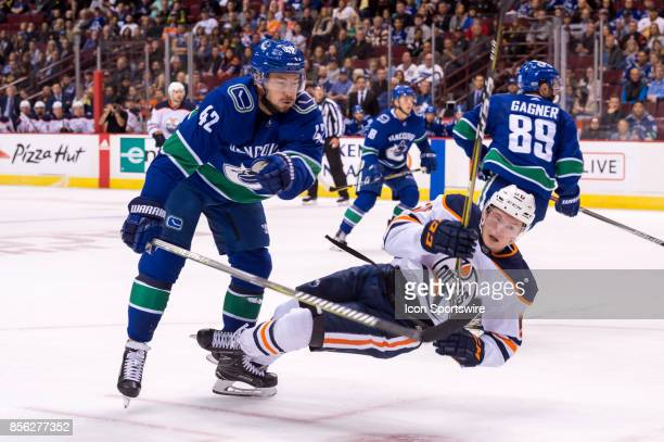 Edmonton Oilers right wing Kailer Yamamoto is checked by Vancouver Canucks center Alexander Burmistrov during their NHL preseason game at Rogers...