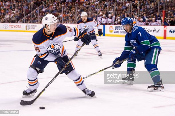 Edmonton Oilers right wing Kailer Yamamoto is checked by Vancouver Canucks right wing Jayson Megna during their NHL preseason game at Rogers Arena on...