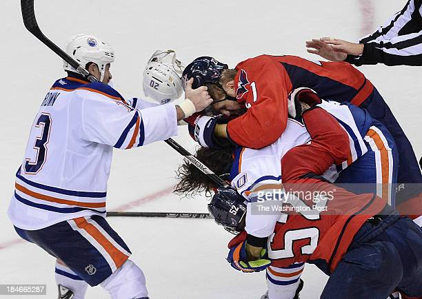 Edmonton Oilers right wing Mike Brown right tries to pull off Washington Capitals defenseman Karl Alzner's helmet as Washington Capitals defenseman...