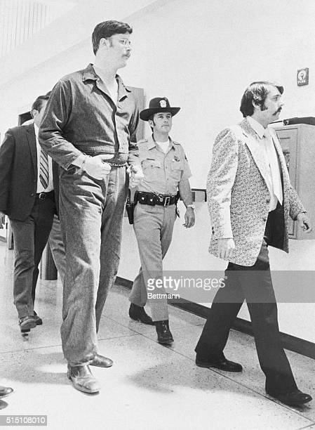 Edmund Kemper III towering above police officers is escorted into Judge Donald May's court 4/30/73 to be arraigned on eight counts of first degree...