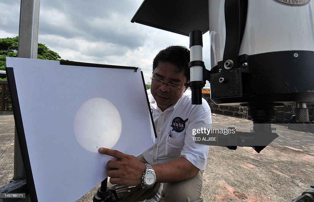 Edmund Rosales, an astronomer from the Philippine Astronomical society, points to the position of Venus, sliding across the sun, on a projection, from a weather observatory in Manila on June 6, 2012. Sky-gazers around the world held up their telescopes and viewing glasses June 6, to watch Venus slide across the sun -- a rare celestial phenomenon that will not happen again for more than 100 years. Other small dots on the right of the photo are called sun spots.