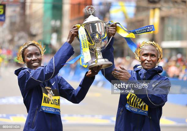 Edna Kiplagat left and Geoffrey Kirui hold up the winner's trophy at the end of the 121st Boston Marathon on April 17 2017