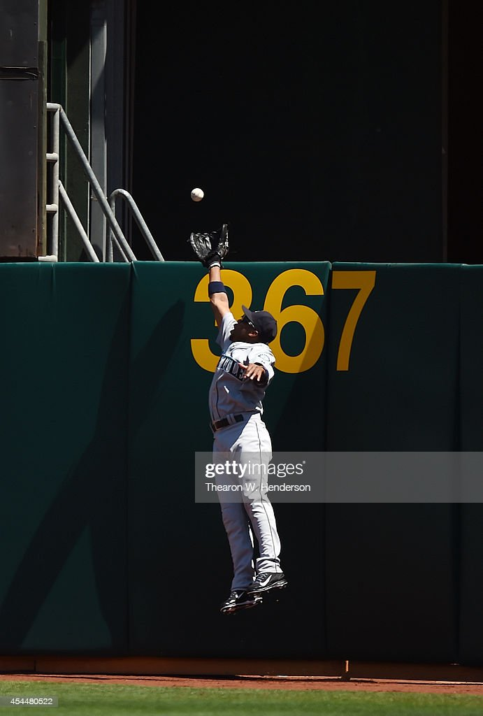 Edny Chavez #9 of the Seattle Mariners leaps at the wall but can't make the catch of this ball that goes for a two-run homer off the bat of Adam Dunn #10 of the Oakland Athletics in the bottom of the first inning at O.co Coliseum on September 1, 2014 in Oakland, California.