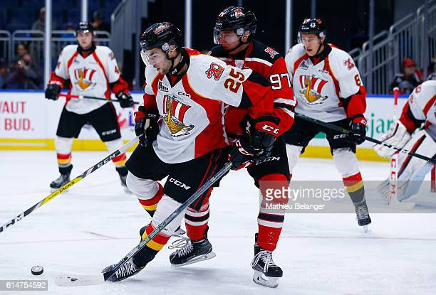 Edouard StLaurent of the Baie Comeau Drakkar and Dmitry Buynitskiy of the Quebec Remparts battle for the puck during their QMJHL hockey game at the...