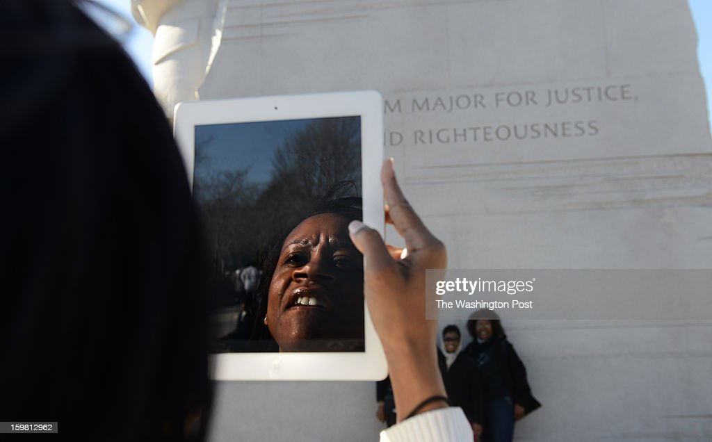 Edra Taylor takes pictures of her friends on her ipad at the Wreath-Laying Ceremony at the Martin Luther King Jr. Memorial in Washington, DC on January 20, 2013. It's the first wreath-laying ceremony since the Memorial was dedicated. Thousands flocked to the area today to pay tribute to the civil rights leader and his legacy. Notables at the ceremony were MLK's oldest son, Martin Luther King III, actor Jamie Foxx, The Rev. Al Sharpton, and Rev. Jesse Jackson.
