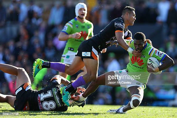 Edrick Lee of the Raiders is tackled by Tim Simona of the Tigers during the round 26 NRL match between the Wests Tigers and the Canberra Raiders at...