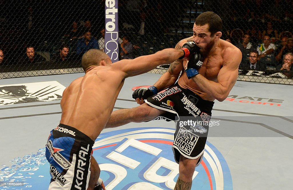 Edson Barboza punches Rafaello Oliveira in their lightweight fight during the UFC 162 event inside the MGM Grand Garden Arena on July 6, 2013 in Las Vegas, Nevada.